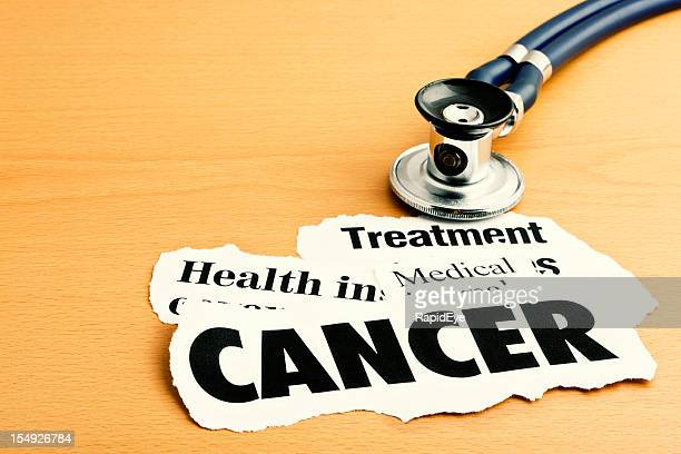 medical stethoscope rests on headlines about cancer and its treatment - single word stock pictures, royalty-free photos & images