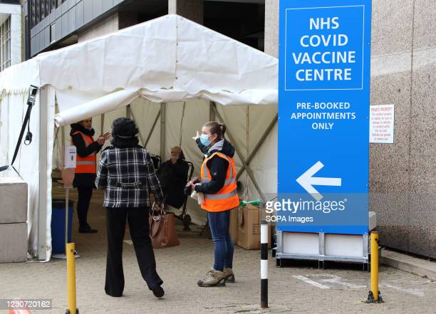 Medical steward wearing a face mask directs people into the vaccination centre. A steady stream of elderly people with pre-booked appointments at the...