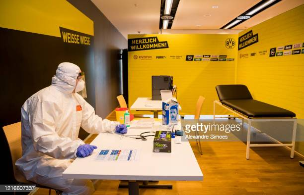 Medical student Florian Schwenzer, wearing protective suits, masks, gloves and goggles sits at a table at the coronavirus care facility at the north...