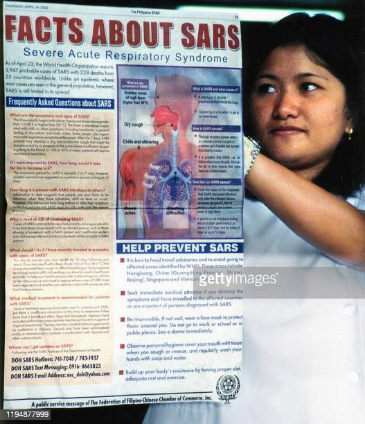 Medical student posts a cut out from the newspaper on SARS in the window of a school building in the city of Baguio, 25 April 2003, as part of a...