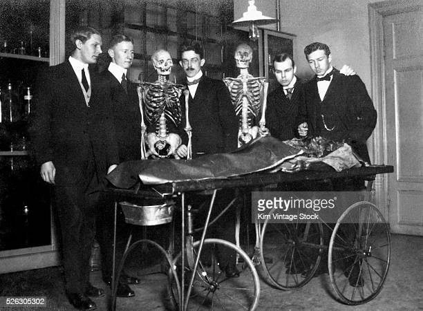 Medical students and some skeletal friends survey a cadaver on a gurney at a hospital in Sweden in the early 20th century