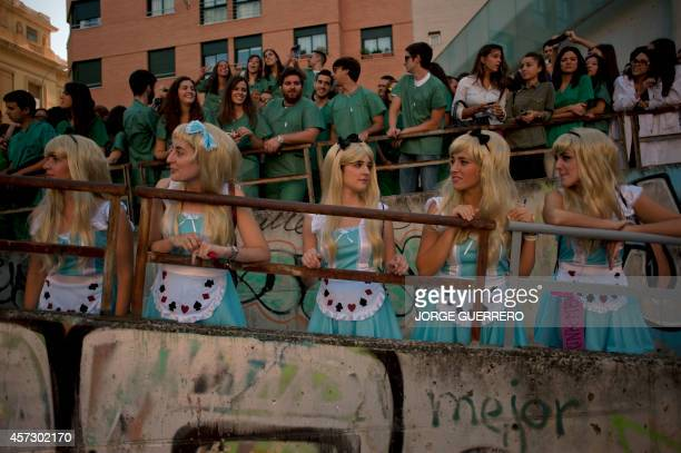Medical students dressed up as the Walt Disney character Alice in Wonderland stand during a faculty of medicine hazing at the University of Granada...