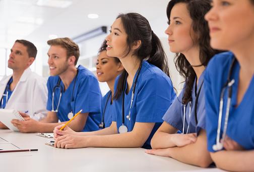 Medical students listening sitting at desk 532548555