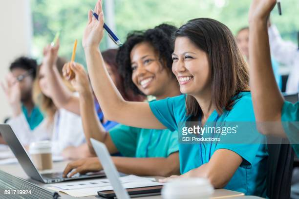 medical students raise hands during class - corsi educativi per adulti foto e immagini stock