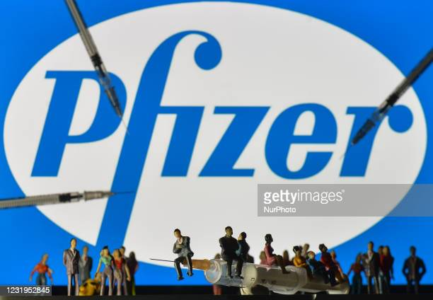 Medical syringes and small figurines of people are seen in front of the Pfizer logo displayed on a screen. On Saturday, March 26 in Dublin, Ireland.