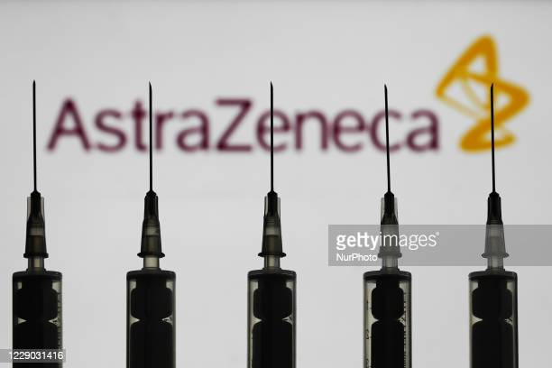 Medical syringes are seen with AstraZeneca company logo displayed on a screen in the background in this illustration photo taken in Poland on October...