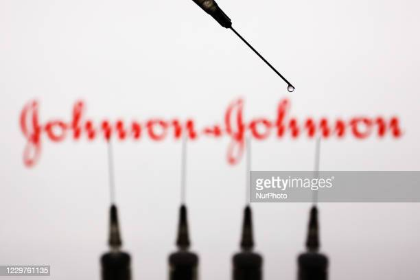 Medical syringes are seen with Johnson and Johnson logo displayed on a screen in the background in this illustration photo taken in Poland on...