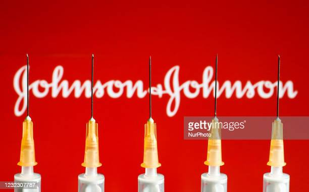 Medical syringes are seen with Johnson&Johnson logo displayed on a screen in the background in this illustration photo taken in Krakow, Poland on...