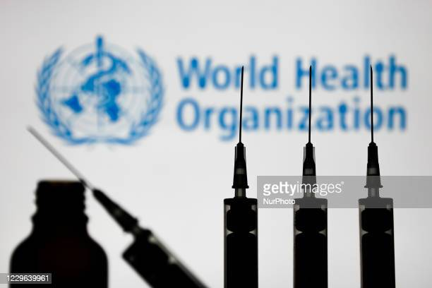 Medical syringes are seen with World Health Organization logo displayed on a screen in the background in this illustration photo taken in Poland on...