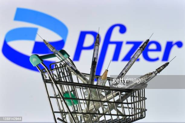 Medical syringes in the mini shopping trolley are seen in front of the Pfizer logo displayed on a screen. On Friday, 28 May 2021, in Dublin, Ireland.