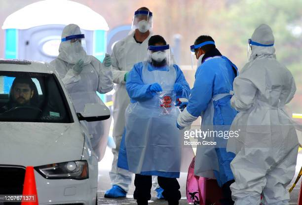 Medical take a patient's coronavirus test during a trial run for a new FEMA drive-thru coronavirus testing clinic at CVS at 720 Boston Turnpike in...
