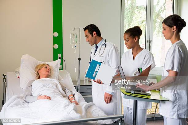 medical team attending female patient on hospital bed - iv infusion stock photos and pictures