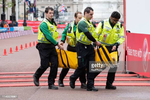 Medical team carries Hayley Carruthers of Great Britain after she crosses the finishing line during the 2019 Virgin London Marathon 28 April London...