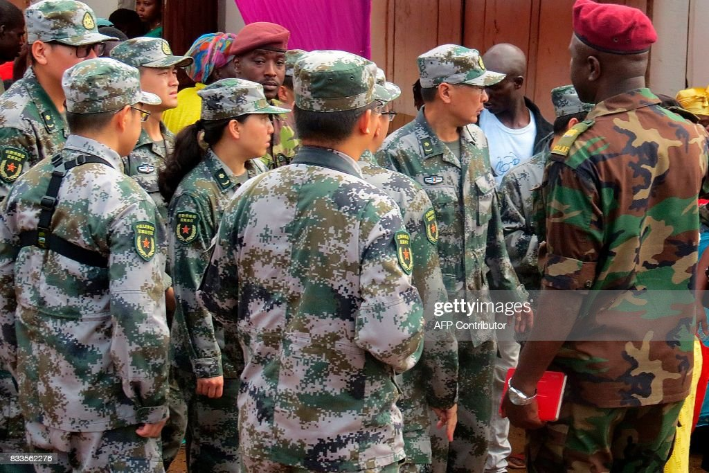 Medical team from the Chinese People's Liberation Army (PLA) speak and meet with local Sierra Leoneans as they arrive close to the site of a huge mudslide in Sugar Loaf mountain, which partially collapsed, in Freetown on August 17, 2017. Sierra Leone began mourning as it emerged that 105 children were among more than 300 people who perished in mudslides and torrential flooding, in one of the country's worst natural disasters on August 14. The government of Sierra Leone, one of the poorest countries in the world, has promised relief for what the Red Cross says is more than 3,000 people left homeless by the disaster. PHOTO / Mohamed Saidu BAH