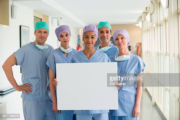 medical team holding a whiteboard - nursing slogans stock photos and pictures