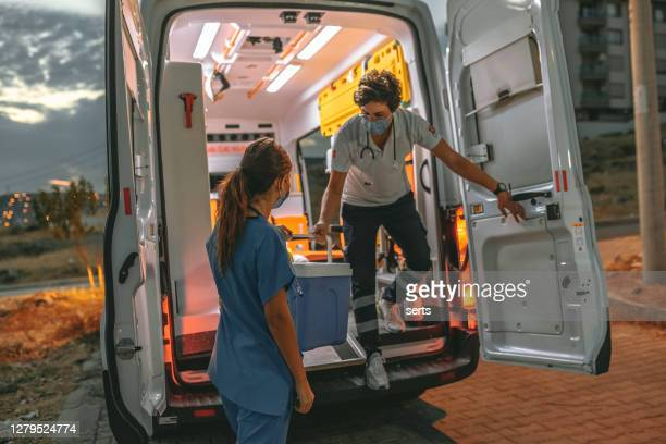 medical team in a hurry carrying organ transplants box by ambulance during pandemic - transportation stock pictures, royalty-free photos & images