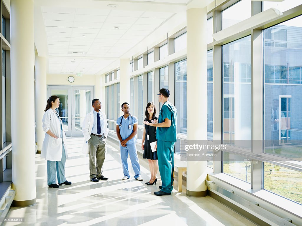 Medical team in discussion in hospital corridor : Stockfoto