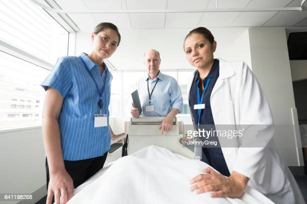 Medical team listening to patient in bed, personal perspective