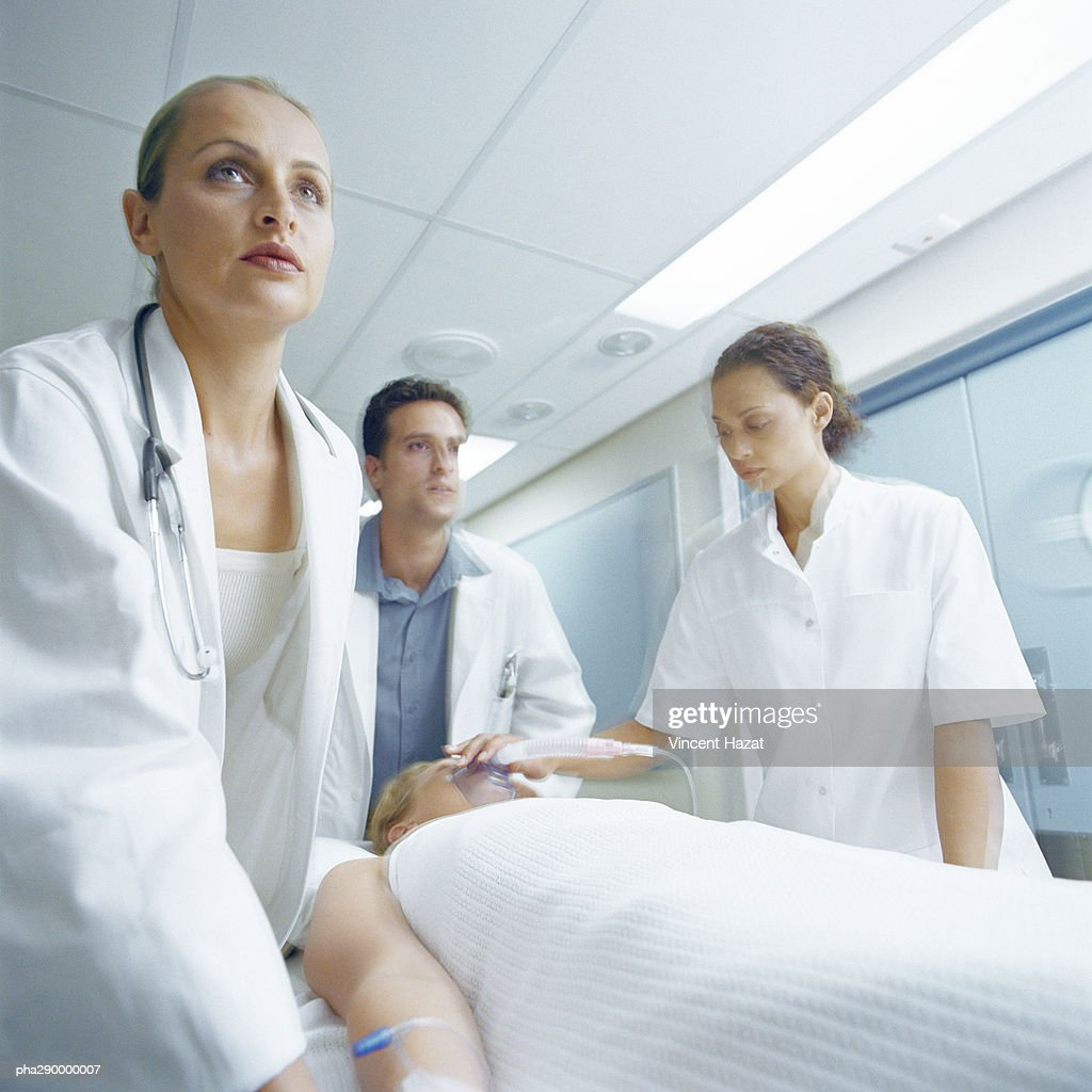 Medical team pushing patient on gurney : Stockfoto