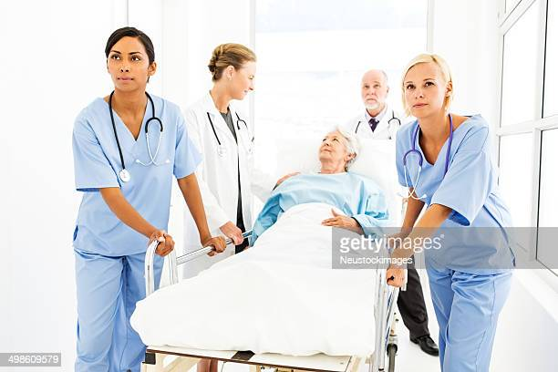 medical team pushing patient on hospital gurney - hospital gurney stock pictures, royalty-free photos & images