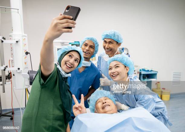 medical team selfie with patient in operating theatre - funny surgical mask stock pictures, royalty-free photos & images