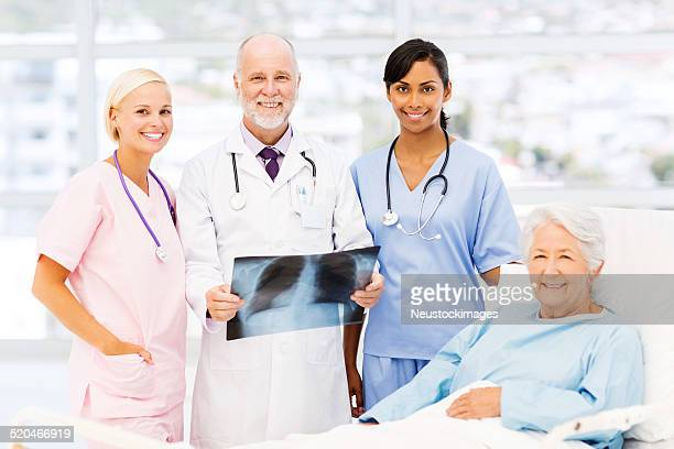 Medical Team Standing By Senior Patient In Hospital Ward