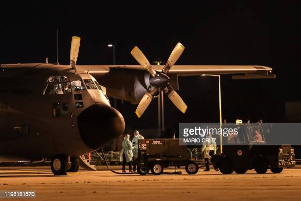 A medical team stands next to a Portugal's Air Force C130 plane carrying Portuguese nationals flown out of the Chinese city of Wuhan the epicentre of...