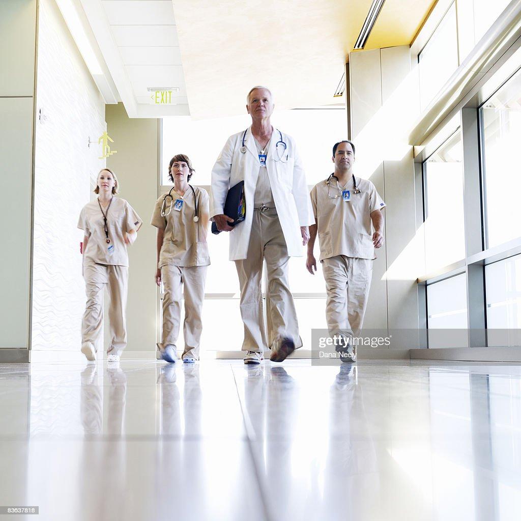 Medical team walking in hospital corridor  : Stock Photo