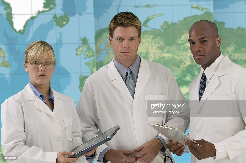 Medical team with tablet computer standing in front of world map : Stock Photo