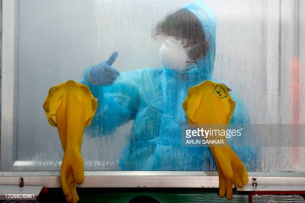 A medical technician gestures at a COVID19 testing and sample collection centre during a governmentimposed nationwide lockdown as a preventive...