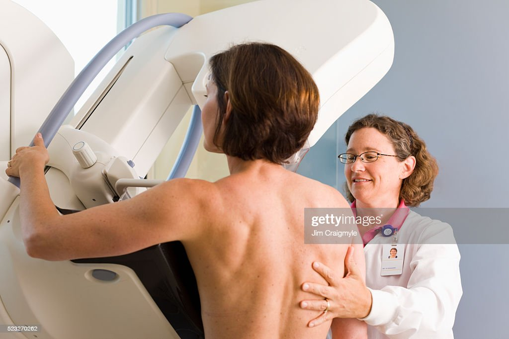 Medical technician preparing patient for mammogram : Stock Photo