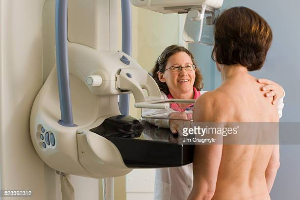 Medical technician preparing patient for mammogram
