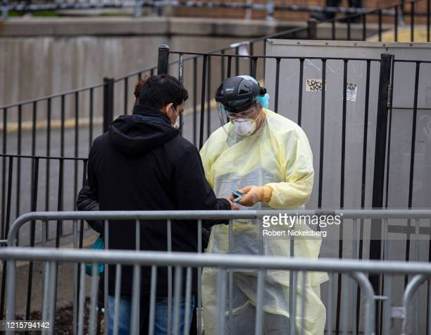 A medical technician right checks a patientu2019s temperature before they enter the Emergency Room with symptoms of possible coronavirus at the...