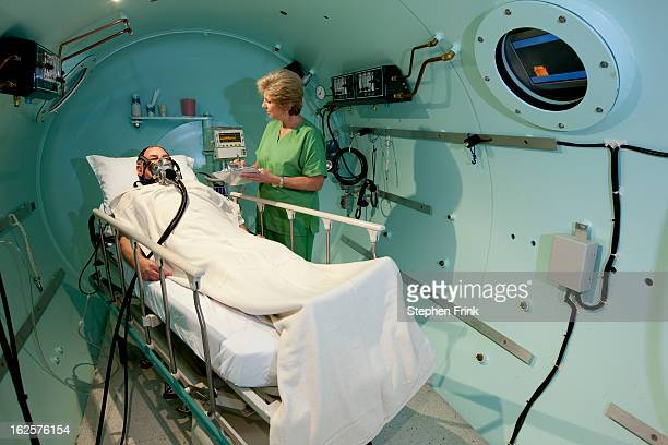 medical treatment inside hyperbaric chamber - oxygen mask stock pictures, royalty-free photos & images