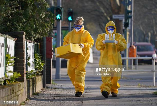 Medical volunteers dressed in protective suits, masks, gloves and goggles return to a medical practice after taking blood and throat mucous samples...