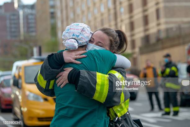 A medical worker and a firefighter embrace outside of NYU Langone Health hospital during the nightly 'Clap Because We Care' cheer for medical staff...