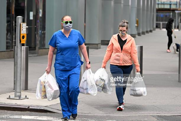 A medical worker and a woman carry groceries while wearing protective masks in Times Square amid the coronavirus pandemic on April 05 2020 in New...