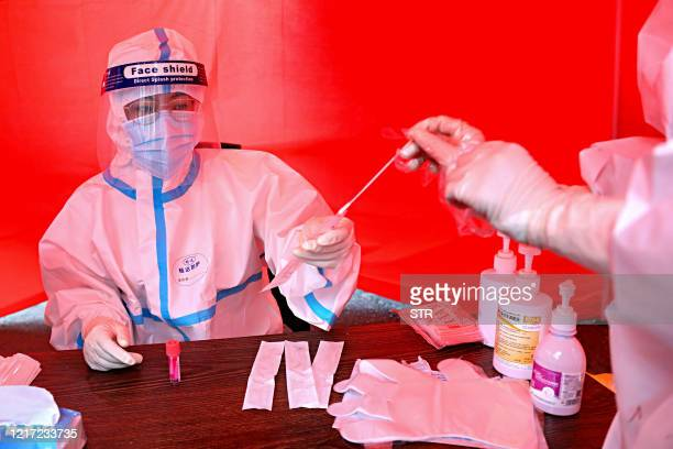 A medical worker collects a sample of a person to be tested for the COVID19 coronavirus on a street in Mudanjiang Chinas northeastern Heilongjiang...
