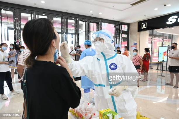 Medical worker collects a throat swab from a staff member for nucleic acid testing at Wanda Plaza on September 11, 2021 in Putian, Fujian Province of...