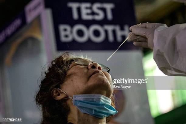 A medical worker conducts a COVID19 swab test on a resident at a basketball court on August 6 2020 in Navotas city Metro Manila Philippines President...