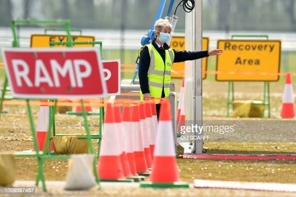 A medical worker directs a NHS worker at a drivein testing station for the novel oronavirus COVID19 at Haydock Park Racecourse in Merseyside North...