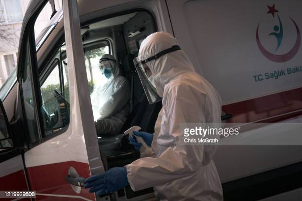A medical worker disinfects the door of his ambulance after dropping off a patient suspected of having the COVID19 virus outside the emergency...