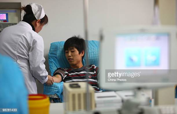 A medical worker draws blood plasma from a student who recovered from A/H1N1 flu at the Shaanxi Blood Center on November 20 2009 in Xian of Shaanxi...