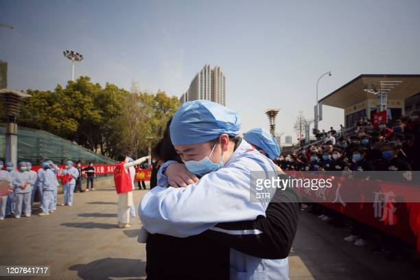 TOPSHOT A medical worker embraces a member of a medical assistance team from Jiangsu province at a ceremony marking their departure after helping...