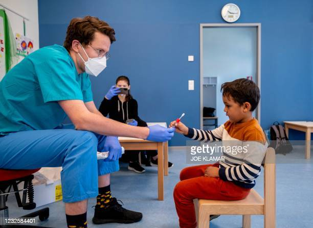 Medical worker gives a pre-school boy a newly developed, lollipop-shaped Covid-19 test prior to the testing of pre-schoolers at the 'City of Vienna...