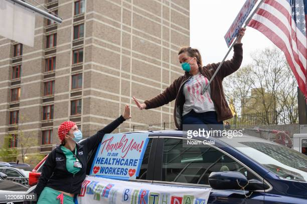 A medical worker gives an air high five to her mother outside NYU Langone Health hospital as people applaud to show their gratitude to medical staff...