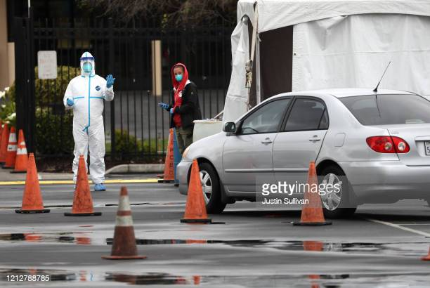 Medical worker guides a car that is going through a coronavirus drive-thru test clinic at the San Mateo County Event Center on March 16, 2020 in San...