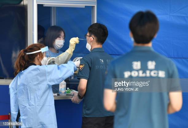Medical worker in a booth takes test samples for the COVID-19 coronavirus from a South Korean police officer at Seoul Metropolitan Police Agency's...