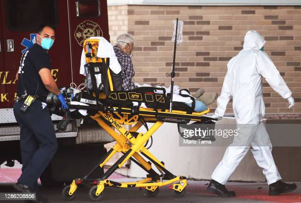 Medical worker in full PPE helps transport a patient into University Medical Center amid a surge of COVID-19 cases in El Paso on November 17, 2020 in...