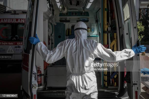 A medical worker in personal protective equipment closes the doors of an ambulance after dropping off a patient suspected of having the COVID19 virus...